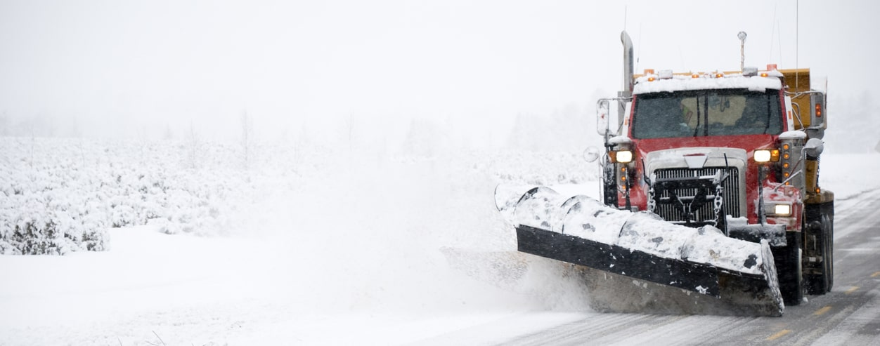 Snow plow pushing snow on road during severe winter weather
