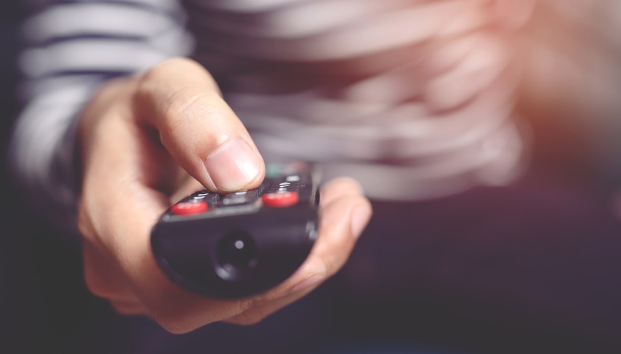 A hand holding a TV remote control pointed toward the camera