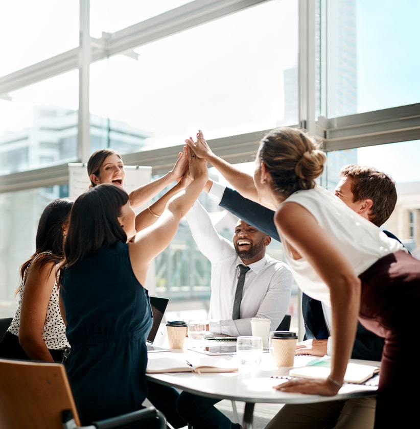 Employee team giving each other high-fives to show teamwork and collaboration