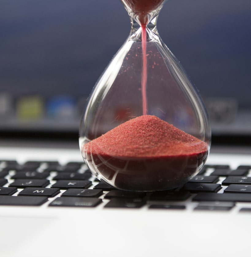 An hourglass sitting on keyboard to suggest a slow website