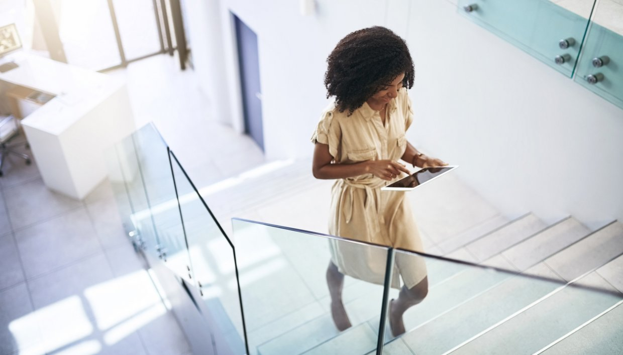 Employee walking up escalator looking at smartphone connected to business WiFi