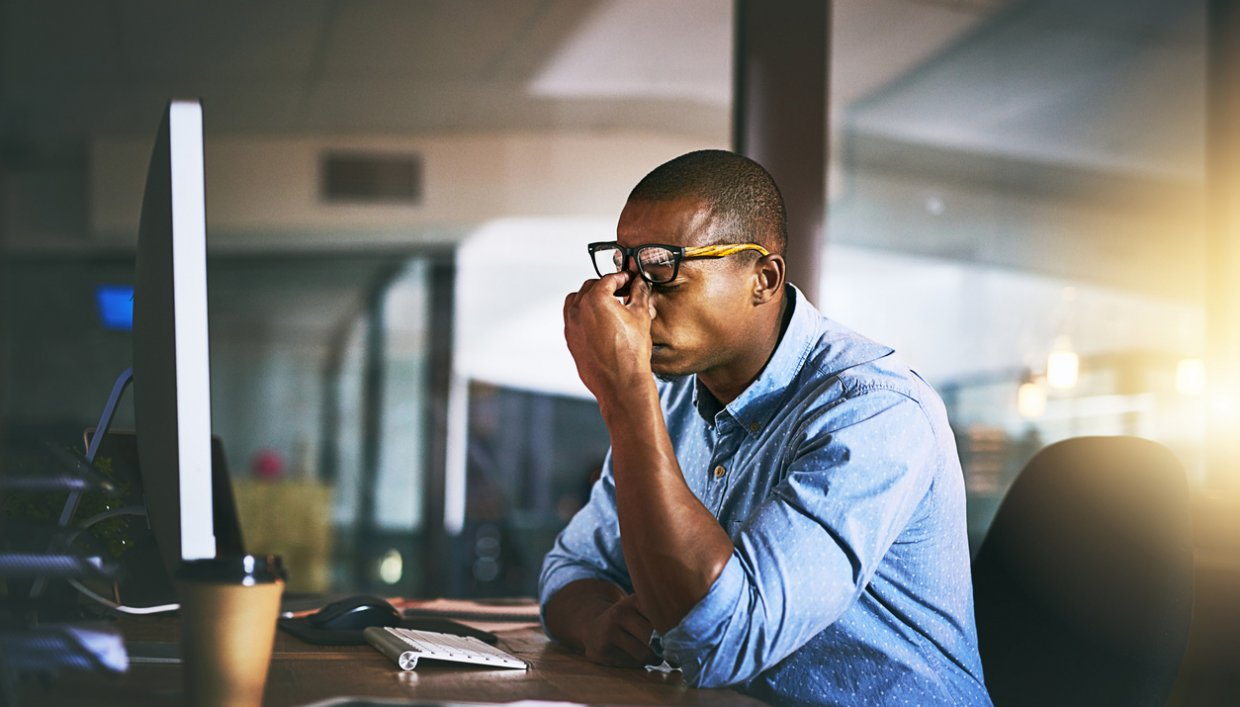 Business owner sitting at computer looking frustrated about slow internet