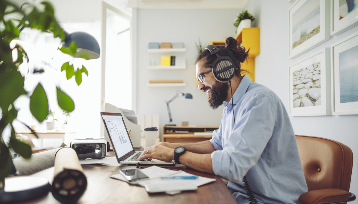 Man working from home on his laptop with headphones