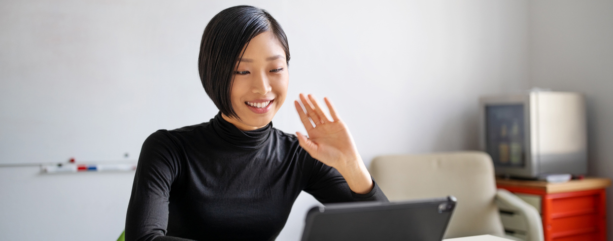 Woman waving to customer over laptop camera