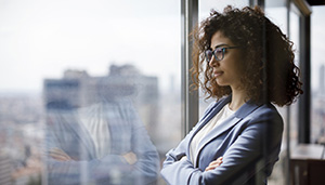 Business woman looking out window thinking about future