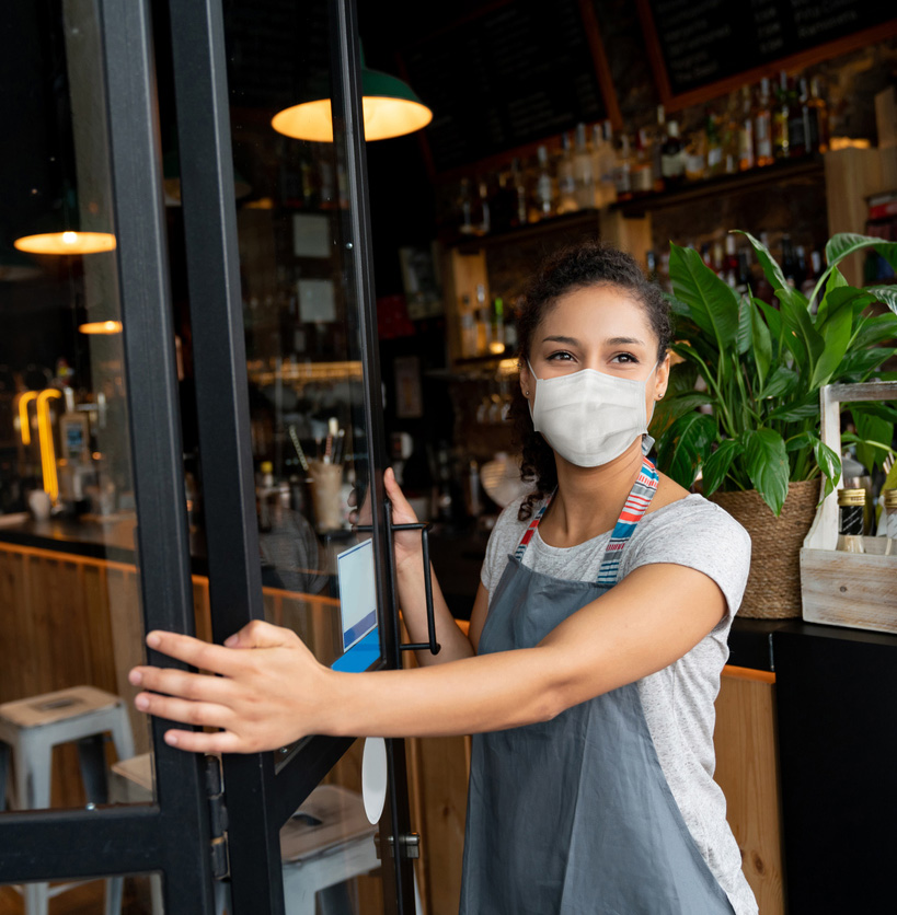 Business owner wearing mask standing in doorway to business