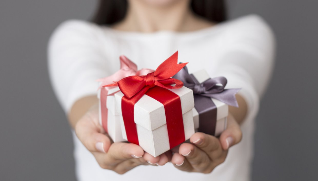 Woman extending arms holding gifts