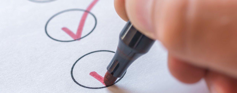 Someone using pen to check off checklist
