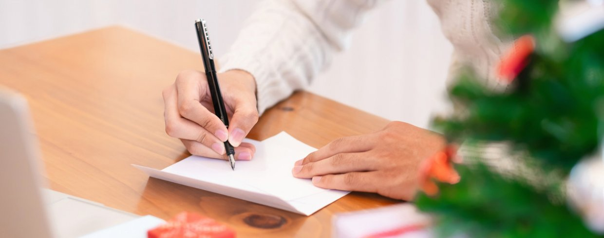 Business owner writing thank-you card to customer over holiday season