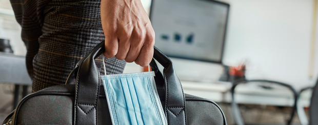 Business owner holding mask next to briefcase as pandemic winds down